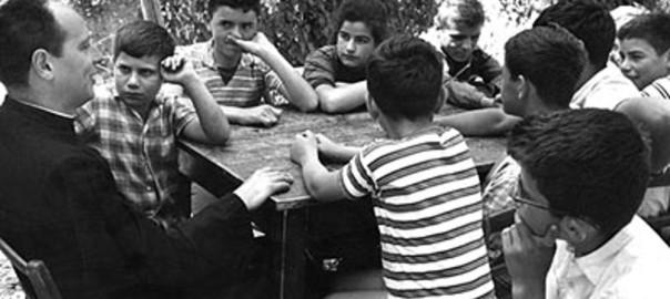 Don Milani al tavolo con dei bambini